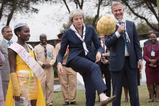 Mrs May shows off her footy skills while former Norwegian politician and Executive Director of the UN Environment Programme Erik Solheim looks on